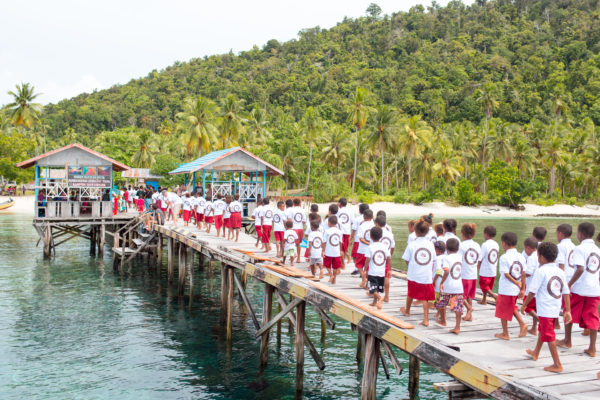 Schoolchildren walk along the pier in Sauwandarek village on Mansuar island; Photo: Indo Yachts Images