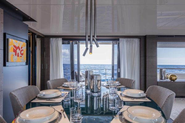 The dining area benefits from sliding doors on each side, and a drop-down balcony to starboard