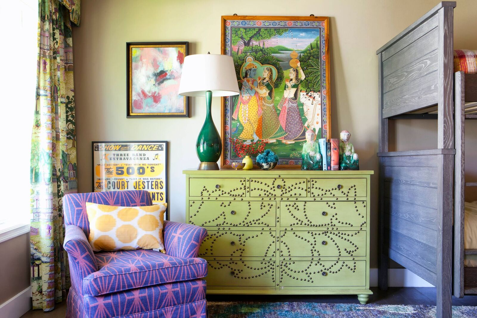 Green dresser with purple chair and large scale art.