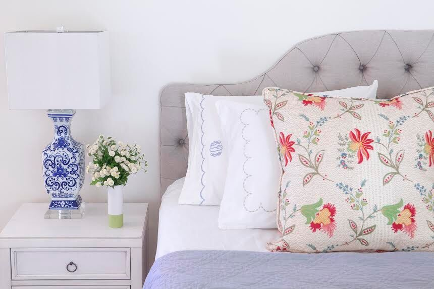 Large scale floral pillow on a grey bed as part of an article on design trends for 2019.